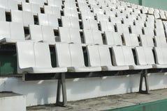 Rader av brutna och nedfläckade vita stolar Arkivfoto