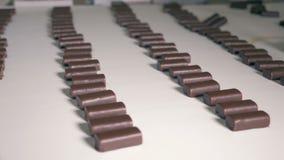 Rader av chokladsötsaker som går ner transportbandet stock video