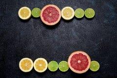 Rader av citruns: citroner, limefrukter och grapefrukt på mörk bakgrund royaltyfri bild