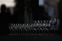 Rader av de tomma vinglasen och rader av tomma exponeringsglas för vodk Arkivbilder