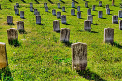 Rader av gammalt, marmor, omärkta allvarliga gravstenar Arkivbild