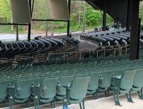 Rader av gröna metallstolar för åhörare på den utomhus- musikmötesplatsen Royaltyfri Bild