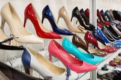 Rader av härliga kvinnors skor på lagerhyllor royaltyfri bild