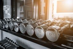 Rader av hantlar 5KG i idrottshallen med monokrom färg tonar Royaltyfri Foto