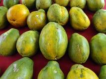 Rader av hawaianska papayas på den röda torkduken Royaltyfri Foto