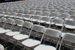 Rader av hopfällbara vita stolar Arkivbilder