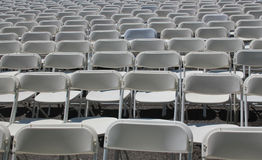 Rader av hopfällbara vita stolar Royaltyfri Foto
