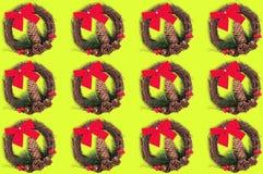 Rader av julkransar med kotten och att fatta av julträdet och röda filialer för pilbåge för textil torra och på gul bakgrund royaltyfri fotografi