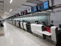 Rader av kontrollerar in räknare på flygplatsen Arkivfoto