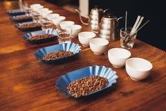 Rader av koppar, exponeringsglas och behållare med kaffebönor Royaltyfria Bilder