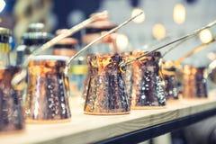 Rader av kopparturks för att laga mat kaffe på kökhylla Selektivt fokusera bakgrundsbokehmusik bemärker tematiskt Arkivbilder