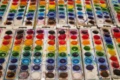 Rader av ljust färgade vattenfärgpannor royaltyfri foto
