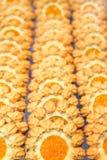 Rader av mördegskakakakor fyllde med jordgubbe- och persikadriftstopp Fotografering för Bildbyråer