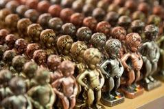 Rader av Manneken Pis metalliska kopior i olika färger Arkivbilder