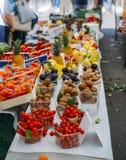Rader av nya frukter som är till salu på ett stånd - selektiv fokus på tomater på förgrund royaltyfria bilder