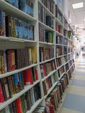 Rader av olika färgrika böcker som ligger på hyllorna i den moderna bokhandeln arkivfoto