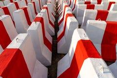 Rader av röda och vita konkreta barriärer som väntar för att användas i trafikkontroll och säkerhet 2 royaltyfri bild