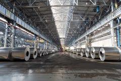 Rader av rullar av den aluminum lögnen i produktion shoppar arkivfoto