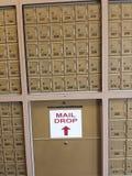 Rader av små metallbrevlådor fodrade mot en vägg med en bokstavsdroppspringa Royaltyfri Fotografi
