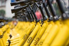 Rader av station-fria delade cyklar för guling OFO Arkivfoto