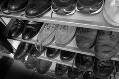 Rader av svartvita gamla skor Arkivbild