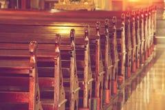 Rader av tomma gamla träkyrkbänkar i historisk kyrka royaltyfri fotografi