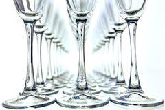 Rader av tomma vinexponeringsglas på den horisontaltabellen Arkivfoto