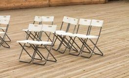 Rader av tomma vita moderna stolar på trägolvet av teatern Arkivbild
