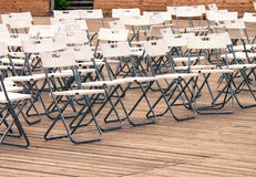 Rader av tomma vita moderna stolar på trägolvet av teatern Arkivfoton
