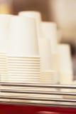 Rader av uppochnervända vita koppar av papp för drycker, disponibel bordsservis för caffeen, utslagsplats, abstrakt icke existera Arkivbild