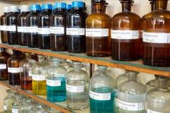 Rader av vätskekemikalieer i flaskor på kemi royaltyfria bilder
