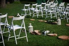 Rader av vita stolar som är ordnade för en bröllopceremoni Royaltyfri Fotografi