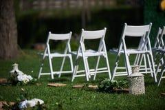 Rader av vita stolar som är ordnade för en bröllopceremoni Royaltyfria Foton