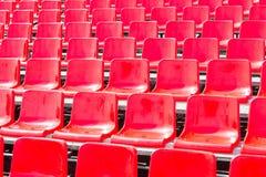 Rader tömmer röda plast- platser i en stadion Fotografering för Bildbyråer
