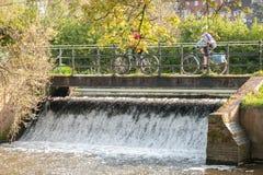 Radfahren über einen Wasserfall Stockbilder