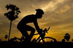 Radfahren auf Sonnenuntergang Lizenzfreies Stockfoto