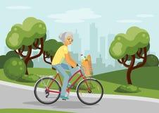 Radfahrende ältere Frau in der Stadt Stockbild