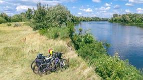 Radfahrenfreien der Familie, Fahrräder nahe Fluss, Vogelperspektive von Fahrrädern und Sturzhelme von oben genanntem, vom Sport u lizenzfreies stockbild