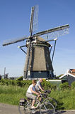 Radfahrensenioren und historische Windmühle Stockfotografie
