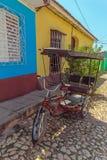 Radfahrentaxi nahe Häusern in der alten Stadt, Trinidad Lizenzfreie Stockbilder