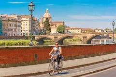 Radfahrer auf Kai vom Arno in Florenz, Italien Stockfotos