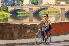 Radfahrer auf Kai vom Arno in Florenz, Italien Stockbild