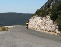 Radfahrer auf schmaler Straße Stockbild