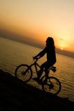 Radfahrer auf Sonnenuntergang. Lizenzfreies Stockfoto