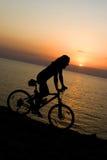 Radfahrer auf Sonnenuntergang. Lizenzfreie Stockfotos