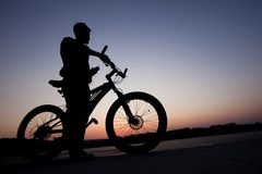 Radfahrer auf Stadthintergrund am Sonnenuntergang Stockfotografie