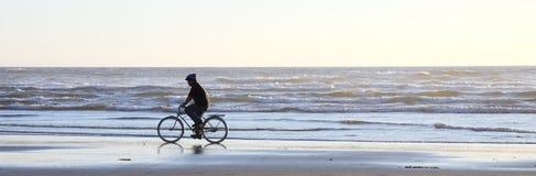 Radfahrer auf Strand am Sonnenuntergang Lizenzfreies Stockfoto
