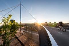 Radfahrer, der über die Stadt-Brücke u. das x28 hinausgeht; Byens-bro& x29; in Odense Denmar Stockbild