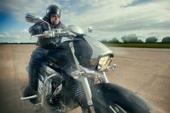 Radfahrer, der auf der Straße auf einem Motorrad läuft Lizenzfreies Stockfoto