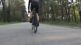 Radfahrer, der auf Fahrradabschluß herauf Beinmuskelansicht radelt Fahrradreiter im Park, der schwarze Sportkleidung trägt Langsa stock video footage